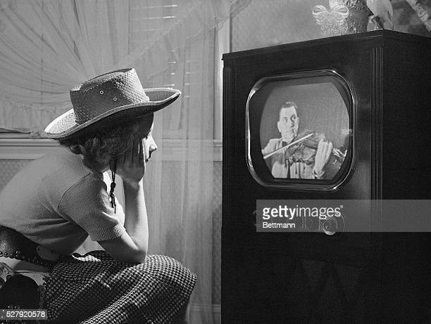 Photo shows a young girl with a straw hat seated, with hand on chin, watching TV. Model: Peggy Ann Baldwin.
