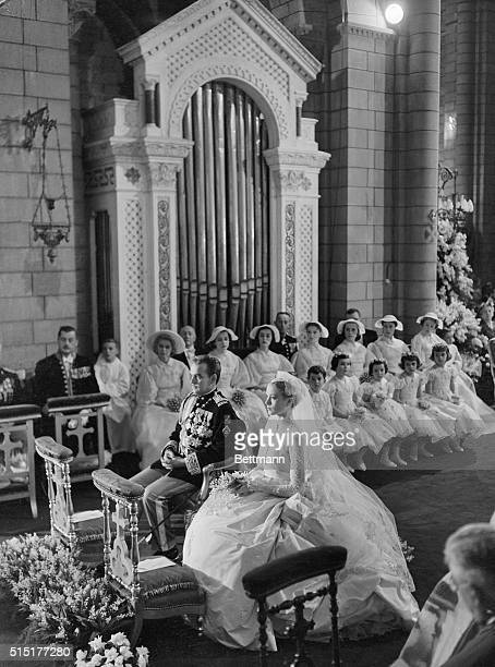 Monaco: Flower girls, page boys, and bridesmaids sit in the background and Prince Rainier and Grace Kelly sit before the altar during their wedding...