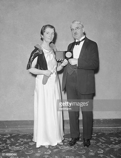 Margaret Sanger distinguished social welfare leader receives the coveted American Women's association medal from Dr John Dewey at the dinner of the...