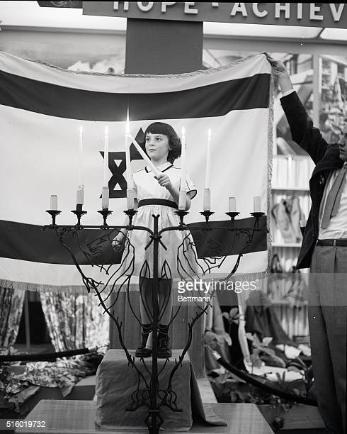 New York, NY: Five year old Rosalyn Kramer, of Dorchester, MA. Is seen lighting candles in honor of Israel's Fifth Anniversary. Photgraph taken at...
