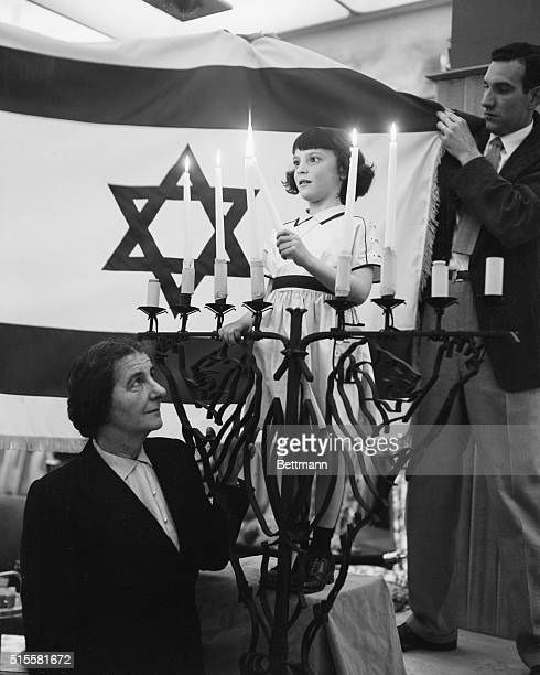 New York, NY: Mrs. Golda Meir, Israel's Chief Delegate to the United Nations, is shown with five year old Rosalyn Kramer, who is lighting five...