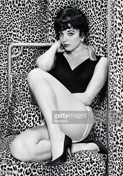 Shapely actress Joan Collins has all the looks of a sultry screen siren as she displays her curves against an exotic leopard skin background Joan...