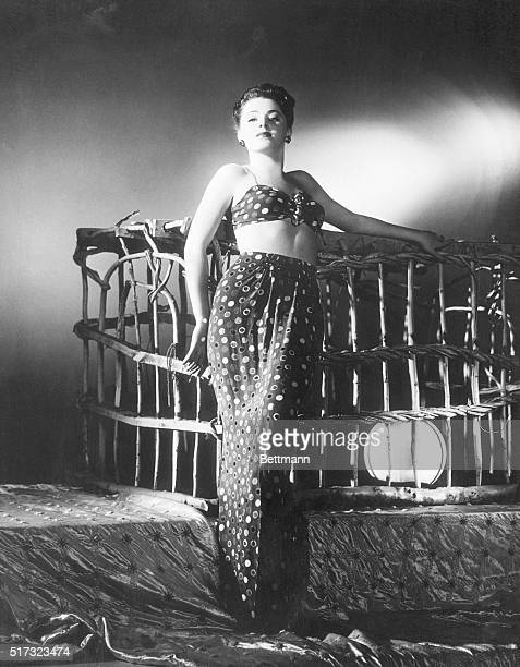 Eleanor Parker, young Warner's player wears a sarong like affair and stands on sumptuos silk quilting. Could she be a flower of the tropics...