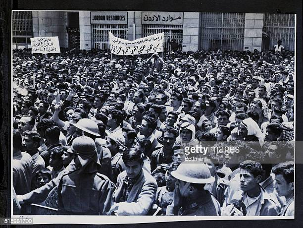 4/24/1957Amman Jordan Steelhelmeted soldiers try to check an angry crowd of bannercarrying demonstrators as they surge through Amman shouting against...