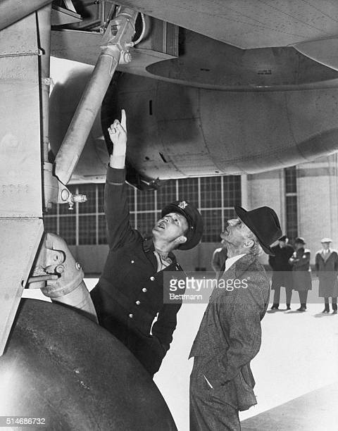 Dearborn, MI: Major B. F. Harmon instructs Henry Ford on a point in the construction of the huge consolidated B-24 bomber which was flown to the Ford...