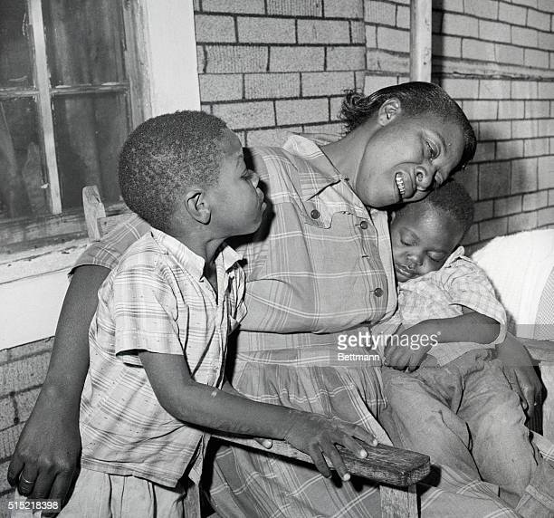 4/25/1959Lumberton MS Mrs Eliza Parker mother of Charlie Parker weeps bitterly as she holds her young son Peanut who sleeps soundly At right is...