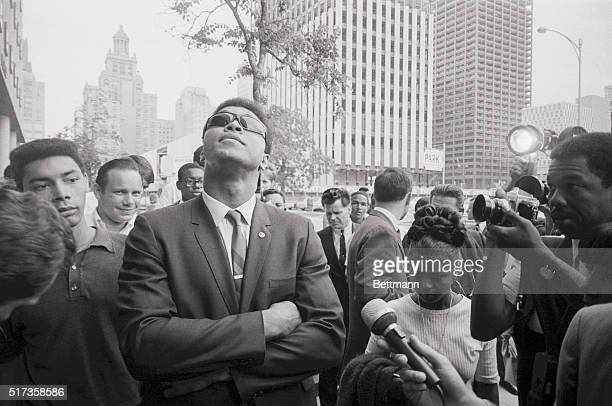 Houston, TX- Surrounded by newsmen and admirers, heavyweight champion Cassius Clay looks skyward as he leaves Federal court in Houston, after a...