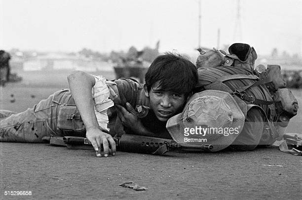 4/28/75Saigon S Vietnam Soldier hangs on to his wounded comrade as they both stay flat on the pavement of the Newport Bridge during a Communist...