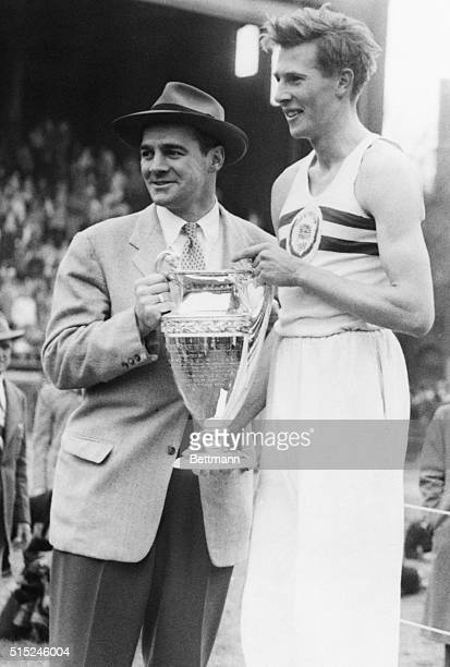 4/29/1951Philadelphia PA British Miler Roger Bannister holds the Winner's Cup after turning in a fast 4083 to easily win the Benjamin Franklin Mile...