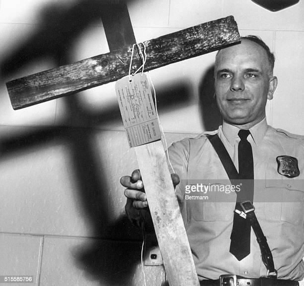 Patrolman John Krok displays the burnt cross that was found in front of the home of Anthony Liuzzo here early 4/3 Mr Liuzzo is the husband of slain...