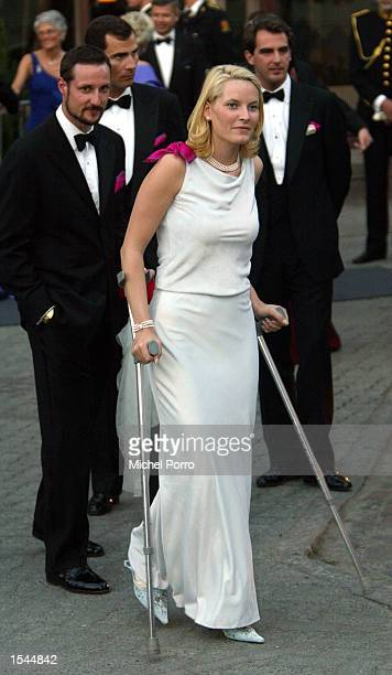 Norwegian Princess Mette Marit is followed by Prince Haakon as she leaves a reception hosted by the government on crutches May 23 2002 in Trondheim...