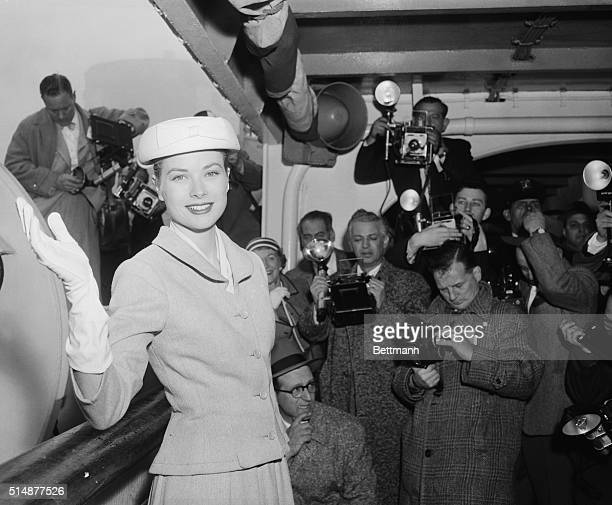 New York, NY: Lovely Grace Kelly graciously waves for the benefit of photographers during her press conference on the sun deck of the S.S....