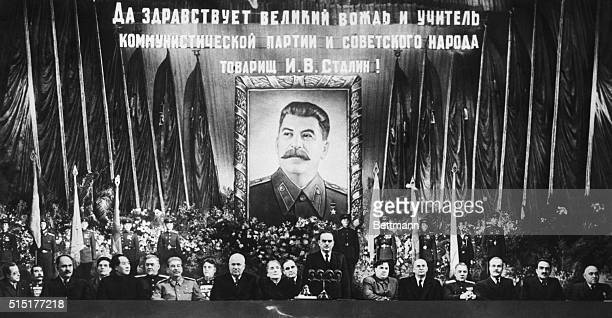 While a huge portrait of the guest of honor beams down from the rear like Big Brother Communist top brass pay honor to Marshall Josef Stalin on the...