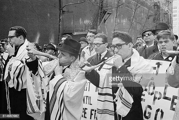 Dressed in religious robes two men blow symbolic reminder of the Battle of Jericho and the collapsing wall before a massive march around the Soviet...