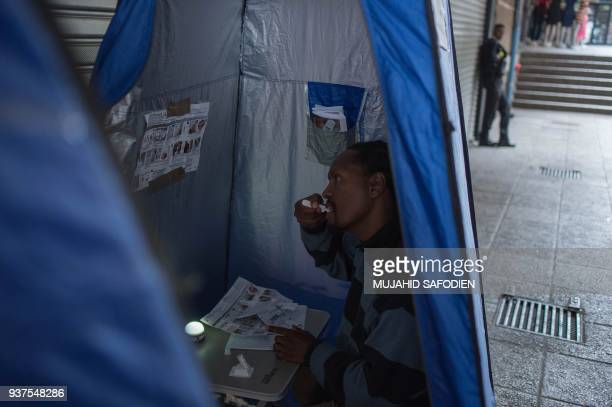 45yearold Oscar Tyumre uses an HIV selftesting kit administered by students from the University of the Witwatersrand in Hillbrow Johannesburg on...