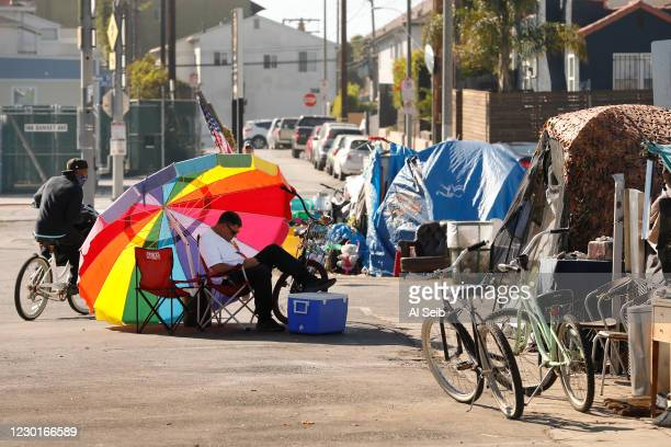 Year-old Richard Thompson seeks the shade of his umbrella as he is camped out with several others in a Venice parking lot across the street from one...