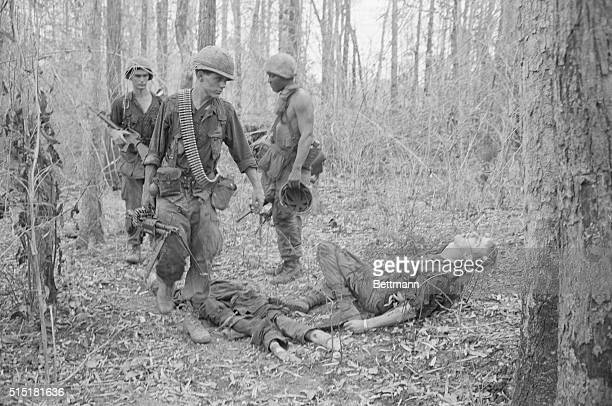 4/6/1967Tay Ninh South Vietnam With a sideward glance at a fallen comrade that says more than words can a soldier pushes on after heavy contact with...
