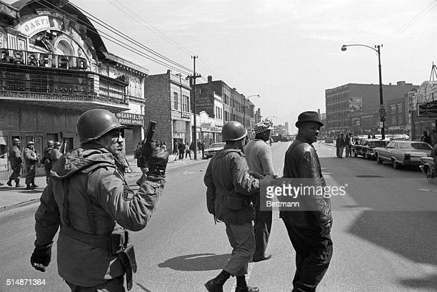 National Guardsmen clear Madison Street of pedestrians and the curious after a night of violence and burning With guns drawn and reportedly loaded...