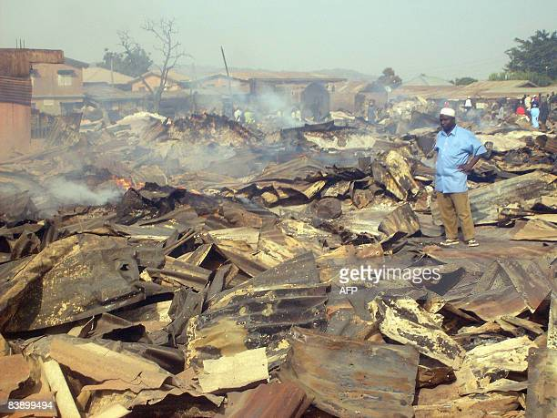 46yearold grain merchant Muhammad Sani looks at the smouldering remains of his shop at Laranto market in Jos on December 3 2008 Over 3000 shops in...