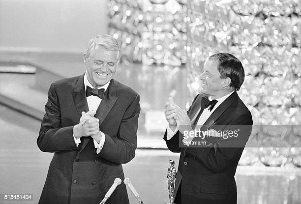 Hollywood, California- As singer Frank Sinatra claps for him, actor Cary Grant holds his hands together as he accepts a special achievement award at...