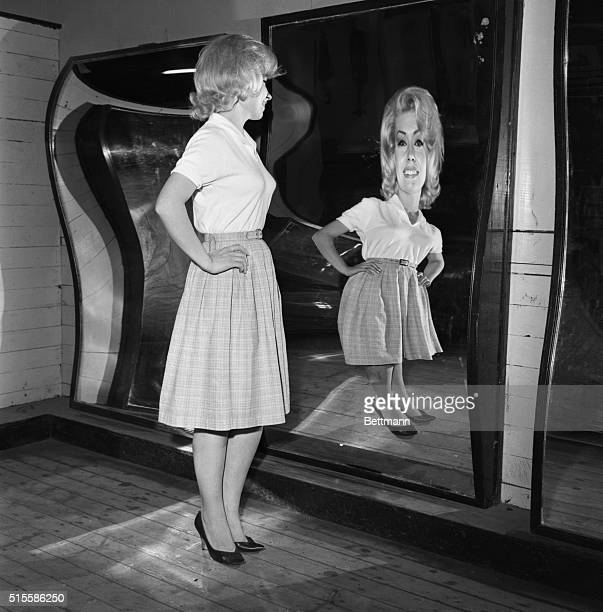 4/8/1963Palisades NJ A slim young lady stands in front of a distorting mirror in the fun house at Palisades Amusement Park in New Jersey She is part...