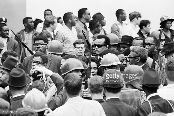 The face of Mrs Martin Luther King Jr is framed by bayonets and helmets of National Guardsmen April 8 as she prepares to lead a memorial procession...
