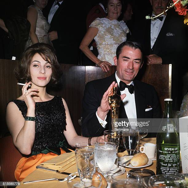 Beverly Hills, CA: Academy Awards party held at the Beverly Hilton Hotel, Berverly Hills CA. Gregory Peck and his wife seated with an Oscar.