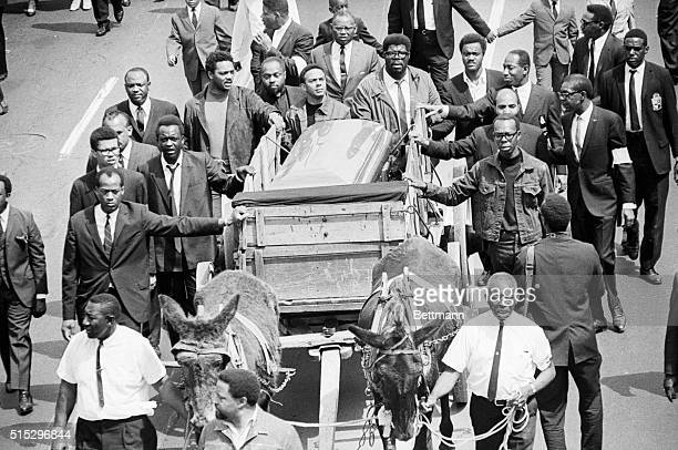 Muledrawn caisson carrying the casket of Dr Martin Luther King Jr is followed by dignitaries and aids as it moves towards the campus of Morehead...