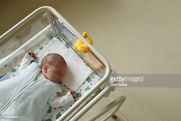 A 4dayold newborn baby lies in a baby bed in the maternity ward of a hospital on August 12 2011 in a city in the east German state of Brandenburg...