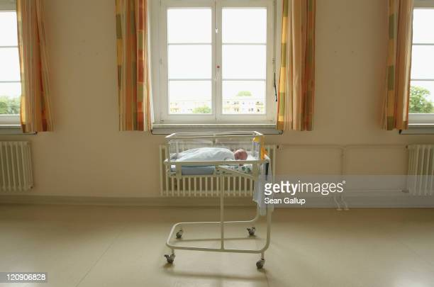 A 4dayold newborn baby who has been placed under a window by the photographer lies in a baby bed in the maternity ward of a hospital on August 12...