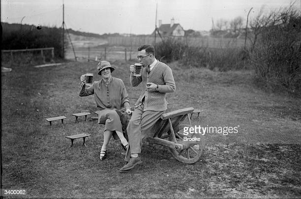 Actor Laddie Cliff enjoying a pint of beer with his new wife Phyllis Monkman after a round of golf in Le Touquet