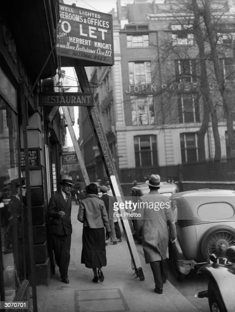 Pedestrians walk under a ladder across a pavement