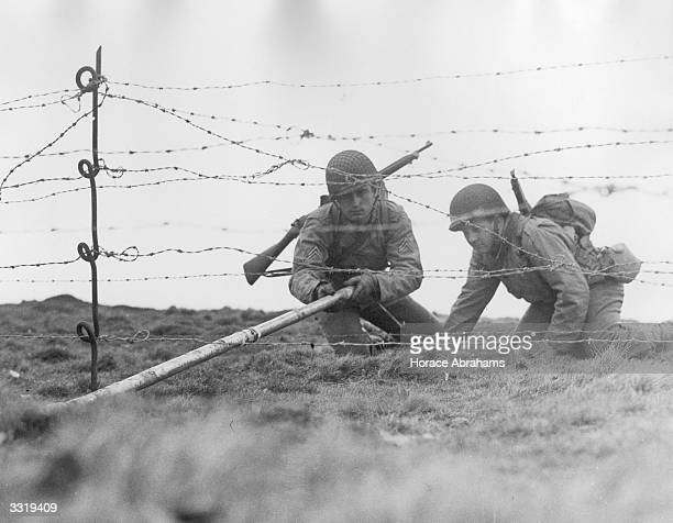US combat engineers place a Bangalore torpedo under a barbed wire fence during exercises under battlefield conditions in the south of England