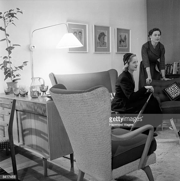 A couple of housewives get comfortable in a sitting room decorated in a modern style on display at the Design And Industries exhibition in London...