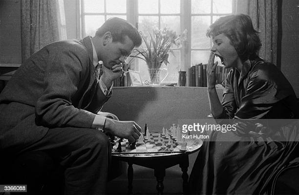 British stage and screen actors Lawrence Ward and a bored Susan Stephen playing chess in their country cottage shortly after their marriage Original...