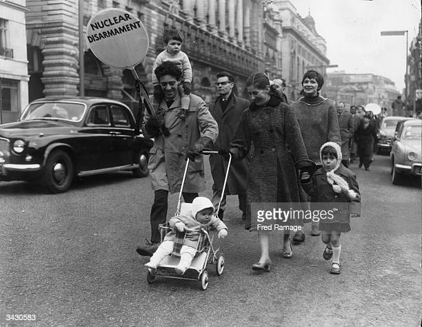 Young couple bring their children with them on a four-day protest march from Trafalgar Square in London to the Atomic Weapons Research Establishment...