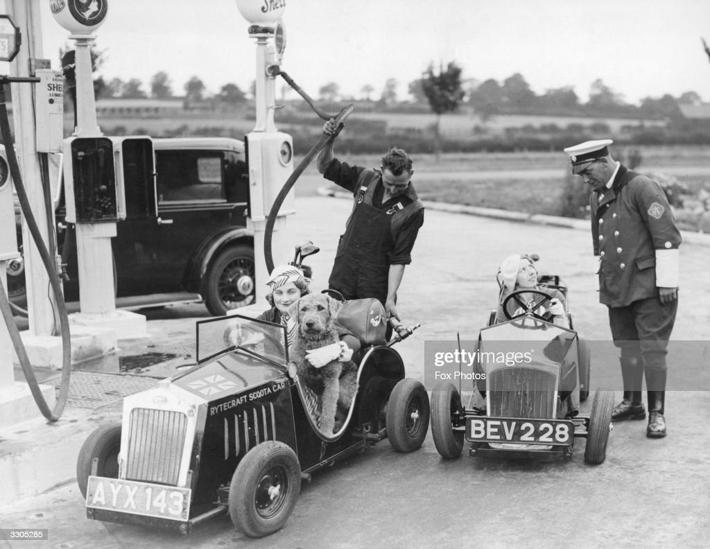 Two drivers in one horsepower cars at a filling station near Barnet, one having her tank filled and the other talking to an RAC motorcyclist. The cars, designed by J W Shillam, are fully licensed for the road and retail at ?70.