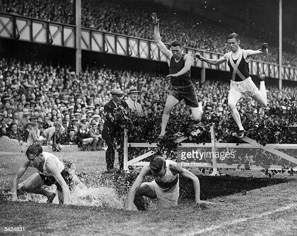 Competitors leaping over the water jump in an eight lap steeplechase event during the 49th annual sports day of the Rangers Football Club held at...