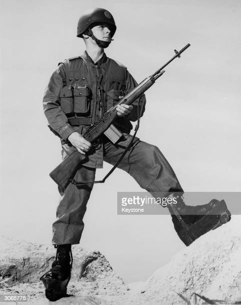 A US Marine wearing experimental battledress comprising a laminated fibreglass helmet body armour and armoured boots and carrying a new M14 rifle He...