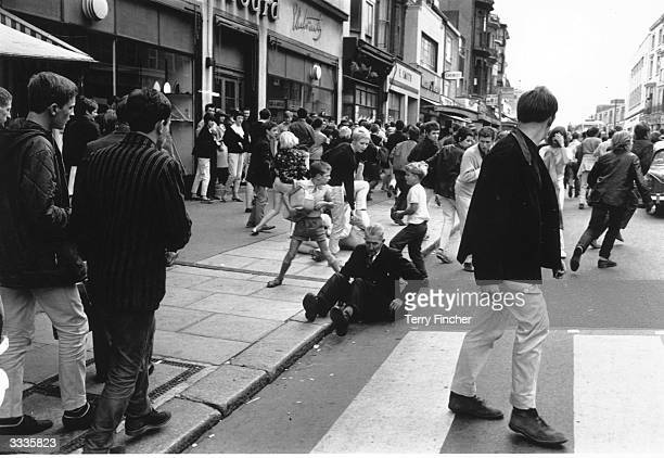 An old man sits on the floor after being caught up in violent clashes between Mods and Rockers at Hastings Kent