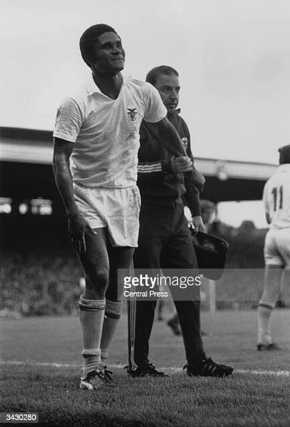 A trainer helping the Benfica and Portugal footballer Eusebio leave the pitch