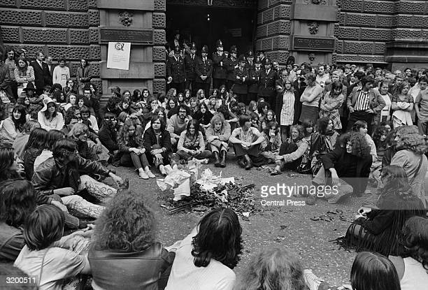 Watched by the police young demonstrators outside the Central Criminal Court of the Old Bailey London burn portraits of Judge Michael Argyle He is...