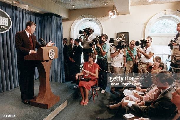 President Ronald Reagan gestures from behind a podium, as reporters and photographers listen at a White House press briefing, Washington, DC.