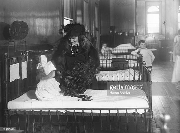Americanborn British politician Nancy Witcher Langhorne Viscountess Astor with a child on a ward at Great Ormond Street Children's Hospital London In...