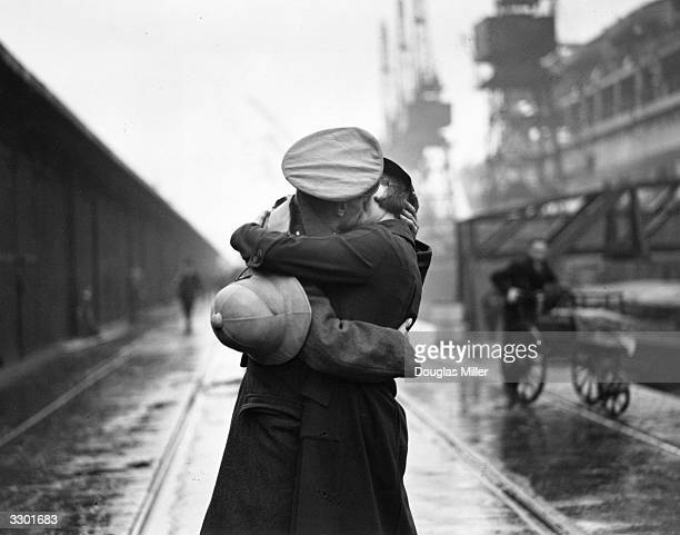 A soldier kissing his wife at King George V's dock London after returning from being stationed in India