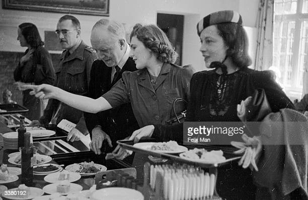 Lord Woolton taking advice on the menu from Mrs Randolph Churchill the assistant secretary during a visit to the Churchill club in Ashburnham House...