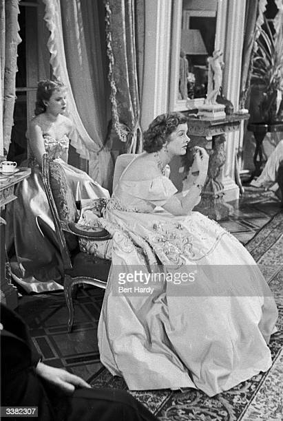 Young Welsh actress Peggy Cummins and American film star Myrna Loy on set during a lull in the filming of the British picture 'That Dangerous Age'...