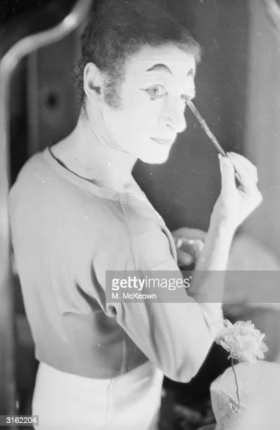 French mime Marcel Marceau applies his famous clown's face paint.