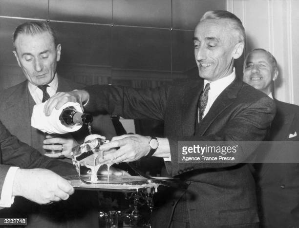 Jacques Cousteau dousing a new type of underwater camera the 'Calypso Phot' with champagne at its unveiling ceremony