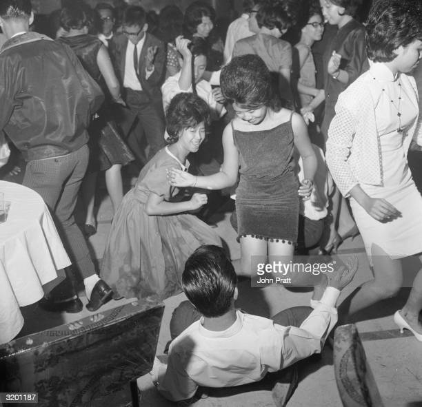 People dancing the twist in the Celestial Room of the Amber Mansion a nightclub in Singapore